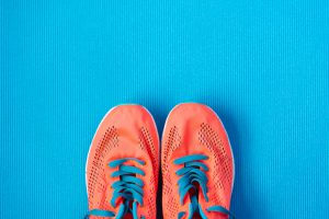 Fitness and gym workout concept. Healthy lifestyle background with sport training shoes close up and blue copy space.